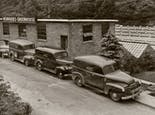 A line of early delivery trucks await product outside our greenhouse, circa 1930