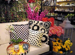 Household furnishings and tall, colorful floral arrangements coexist on our showroom floor