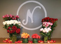 Flaunted by bouquets, the Neubauer's logo is painted on a gray wall
